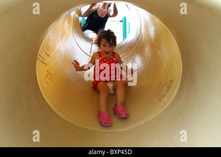 Una bambina gode la sua giornata sulle diapositive a spruzzo Locale parco in Charlottesville, Virginia. Foto Stock