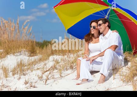 Uomo e donna coppia romantica sotto un colorato ombrellone o ombrellone in spiaggia Foto Stock