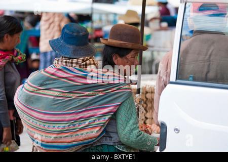Signora boliviana in abito tradizionale con un giovane bambino in imbracatura sulla sua schiena, Huari, Bolivia, Foto Stock