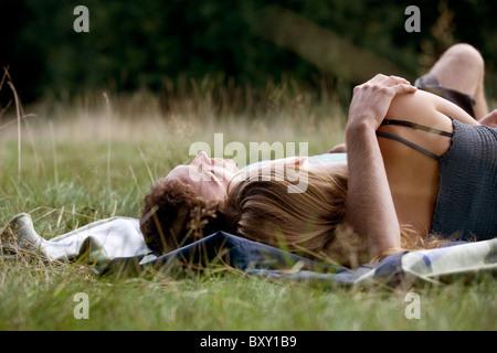 Una giovane coppia sdraiati sull'erba Foto Stock