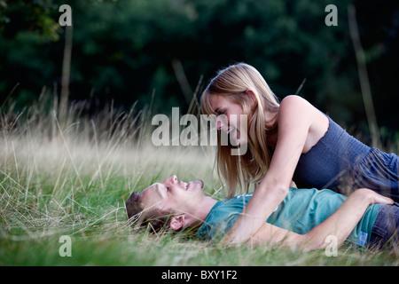 Una giovane coppia sdraiati sull'erba, ridendo Foto Stock
