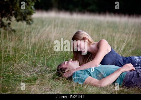 Una romantica coppia giovane sdraiati sull'erba Foto Stock