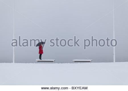 Figura solitaria di una giovane donna che indossa un cappotto rosso con ombrello in piedi su una panchina nella Foto Stock
