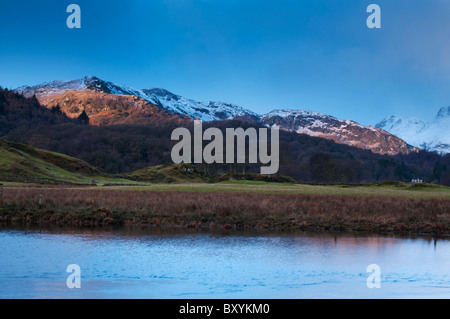 Il sole illumina la neve e rabboccato fells a Elterwater nella grande Langdale Valley, Lake District Foto Stock