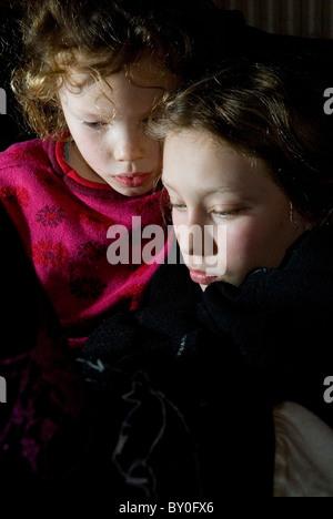 Due giovani sorelle la riproduzione di un lettore portatile di console per i giochi, le loro facce illuminato dallo Foto Stock