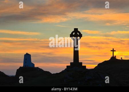 St Dwynwen croce celtica e Twr Mawr faro in silhouette sull isola di Llanddwyn al tramonto Isola di Anglesey, Galles del Nord, Regno Unito