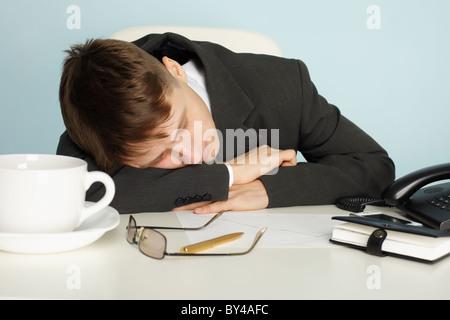 Un giovane lavoratore di ufficio era stanco e si è addormentato al tavolo Foto Stock