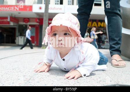 Dieci mesi ragazza bambino gattona con sua madre dietro a guardare oltre la sua Foto Stock