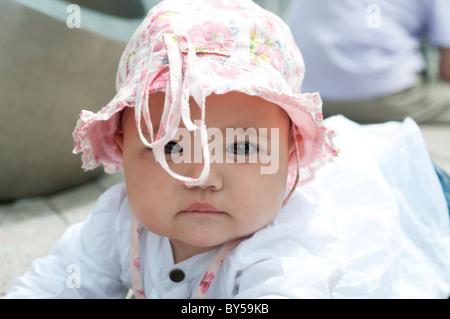 Dieci mesi di età ragazza con cappello rosa di guardare direttamente la fotocamera Foto Stock
