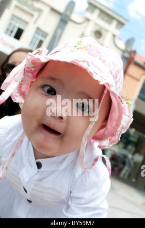 Dieci mesi ragazza bambino guardando intensamente la fotocamera Foto Stock