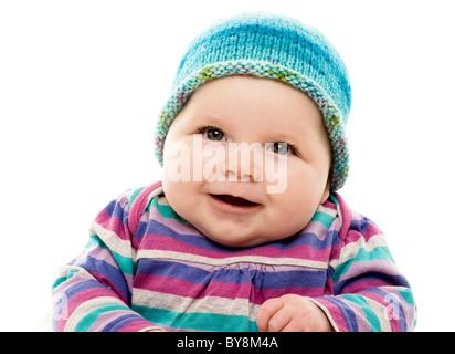Testa e spalle colpo di bambino in Colorati luminosamente striata vestito e turchese hat Foto Stock