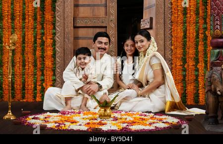 Sud famiglia indiana con fiore rangoli Foto Stock