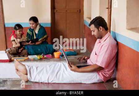 Uomo rurale lavorando sul suo computer portatile Foto Stock