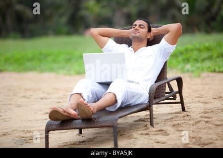 L'uomo prendendo un pisolino in una spiaggia Foto Stock