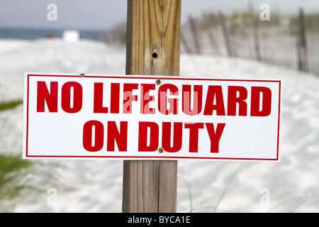 Il segno inviato a una spiaggia notifica nuotatori che non vi è alcun bagnino di turno. Foto Stock