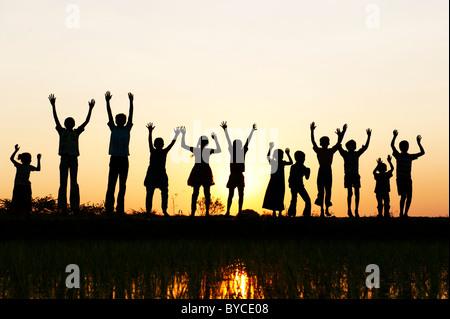 Silhouette Indian ragazze e ragazzi saltando e agitando in piedi su un riso risaie al tramonto. Andhra Pradesh, Foto Stock