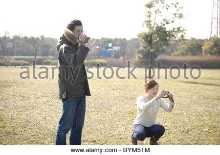 Metà Adulto Giovane utilizzando telecamere Foto Stock