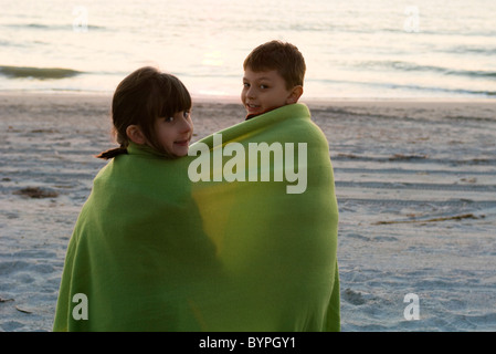 Bambini avvolti insieme in una coperta sulla spiaggia Foto Stock