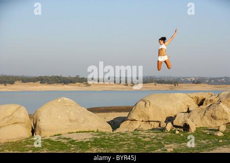 Una donna salti di gioia su alcune rocce Foto Stock