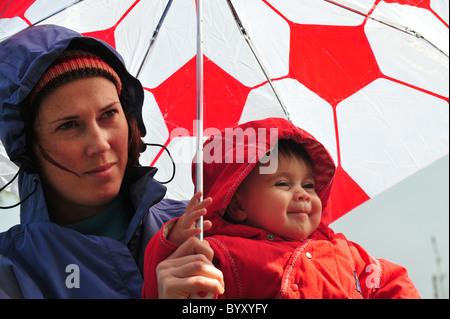 La madre e il bambino sostare sotto un ombrello guardando la caduta di pioggia in un giorno di inverni . Foto Stock