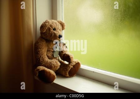 Orsacchiotto di peluche guarda fuori della finestra Foto Stock