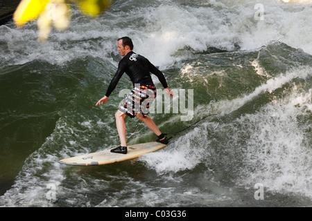 Surfer su un onda nel flusso Eisbach, il Giardino Inglese di Monaco di Baviera, Baviera, Baviera, Germania, Europa Foto Stock