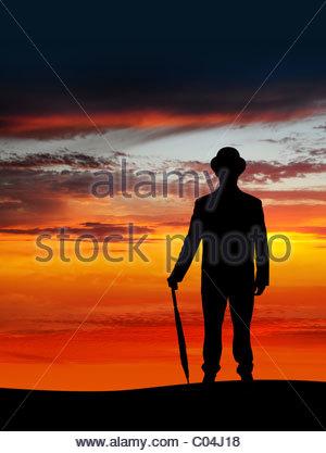 Imprenditore tenendo un ombrello in sunset Foto Stock