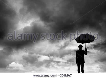 Imprenditore tenendo un ombrello in una tempesta Foto Stock