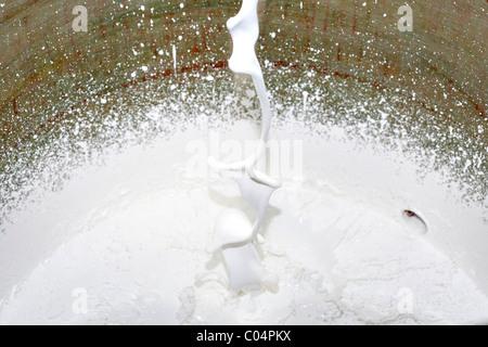 Flusso di vernice bianca cade in una benna Foto Stock