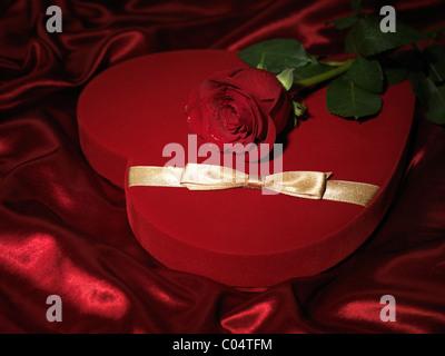 Cuore rosso a forma di scatola regalo e una rosa rossa