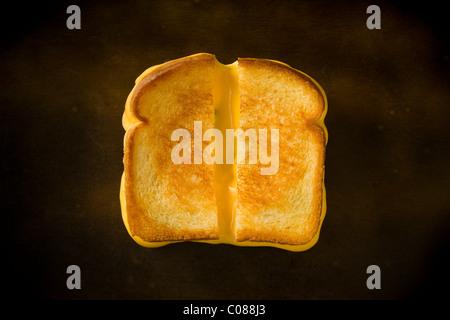Un formaggio alla griglia panino tagliato a metà tirando il formaggio su una tavola di legno Foto Stock