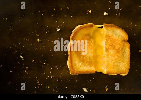Un formaggio alla griglia panino tagliato a metà tirando il formaggio su una tavola di legno