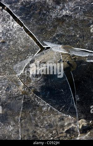 Close up dettaglio dei modelli di ghiaccio in un'acqua di disgelo Congelato stagno causato da un improvviso cambiamento Foto Stock