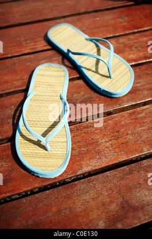Blu Marrone flip flop sul pianale in legno Foto Stock