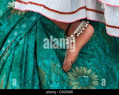 Bambini indiani piedi nudi contro le madri floreale verde sari. Andhra Pradesh, India Foto Stock