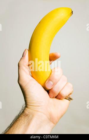Maschio di mano che tiene una banana come una pistola isolato su un punto grigio neutro/sfondo bianco per intaglio Foto Stock