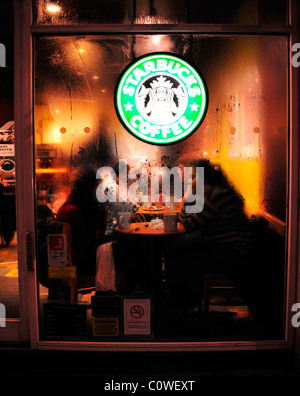 La gente attraverso steamy finestra avente un caffè a Starbucks Coffee Bar di Londra Foto Stock