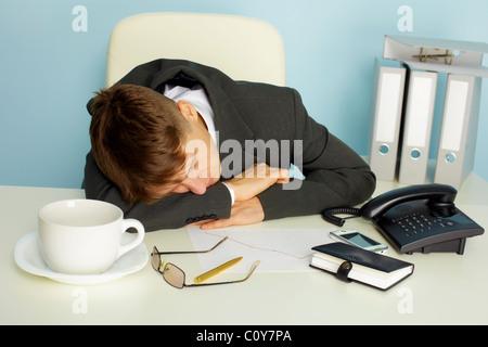 Il giovane uomo è caduto addormentato sulla scrivania in ufficio Foto Stock