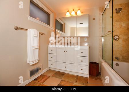 Classici beige bagno con bianco e armadi in legno piastrelle e