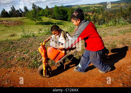 Due ragazzi spingendo la rottura di un triciclo, Indiani Mapuche, vicino a Concepción, nel sud del Cile, Cile, Sud Foto Stock