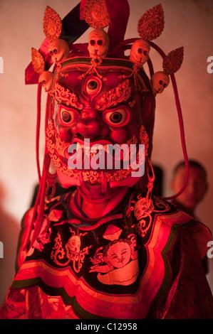 Monaco buddista vestito di danza rituale del costume che rappresenta un dio o un demone si prepara a ballare a un festival religioso