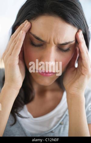La donna che soffre di mal di testa tenendo la testa in mani Foto Stock