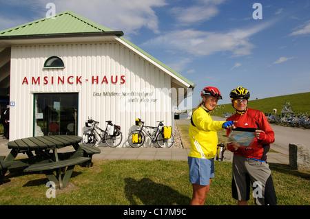 I ciclisti di fronte alla casa Amsinck vicino ad Amburgo Hallig, Frisia settentrionale, il Mare del Nord, Schleswig Foto Stock