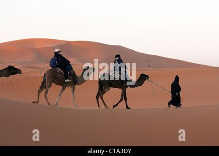 I turisti su un cammello viaggio di campeggio a sunrise nel deserto del Sahara, Erg Chebbi, Marocco. Foto Stock