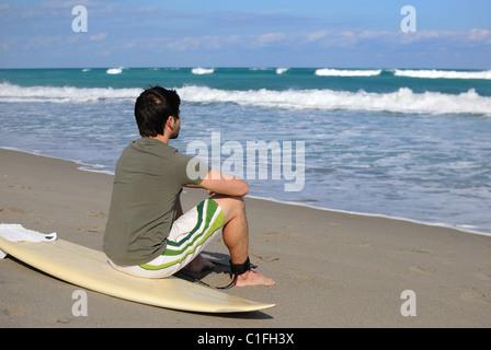 Surfer sulla spiaggia con il suo bordo. Foto Stock