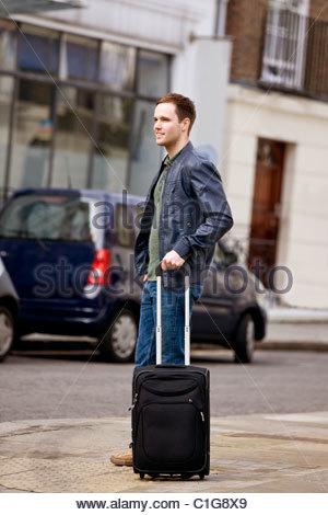 Un giovane uomo in piedi in strada, tenendo la sua valigia Foto Stock