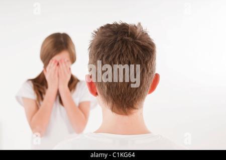 Ragazzo che guarda alla ragazza con la faccia coperta Foto Stock