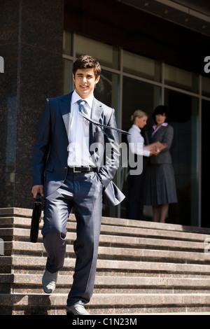 Ritratto di imprenditore fiducioso a piedi giù per le scale con interazione donne dietro Foto Stock