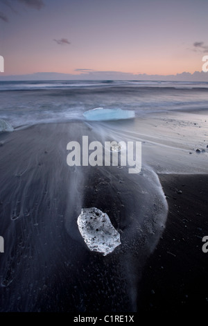 Iceberg sulla spiaggia nera con il lavaggio della marea intorno a loro in Islanda Foto Stock