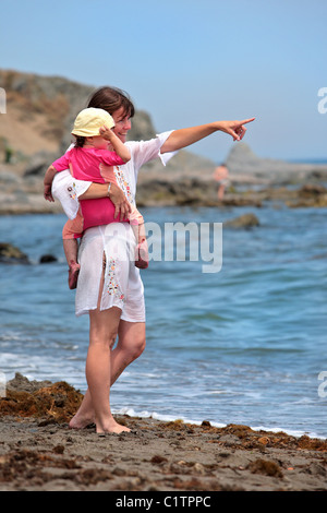 Una giovane madre rimanda a qualcosa di fuori in mare mentre portando la sua bimba sulla spiaggia in una luminosa Foto Stock